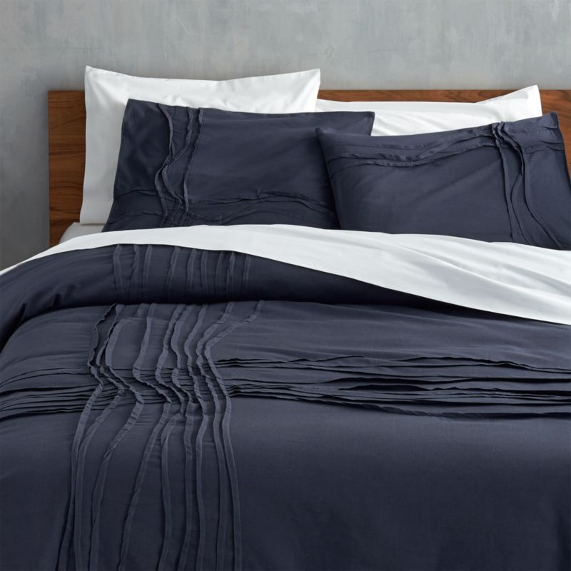 "<span class=""copyHeader"">monochromatic merge.</span> Navy-on-navy sleepscape dreams up tone-on-tone texture. Woven of soft cotton/linen, flowing ribbons of fabric cross paths off-center in an organic ripple effect. Duvet reverses to solid navy. Duvet has non-slip corner ties and hidden button closure.<br /><br /><NEWTAG/><ul><li>Cotton/linen</li><li>250 thread count</li><li>Duvet has non-slip corner ties and hidden button closure; reverses to solid navy</li><li>Machine wash</li></ul><br />"